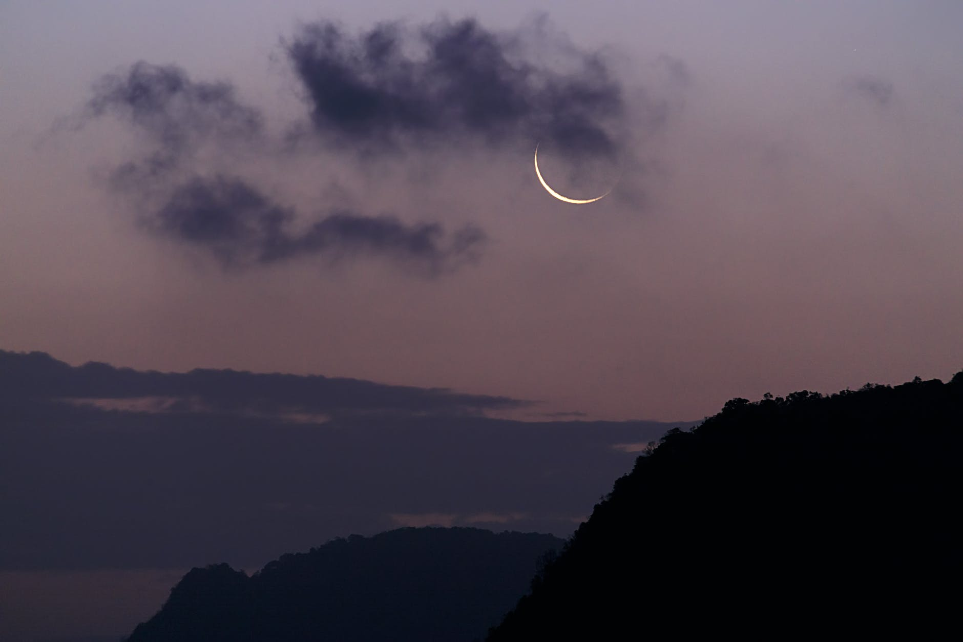 silhouette of mountain under the moon covered with clouds