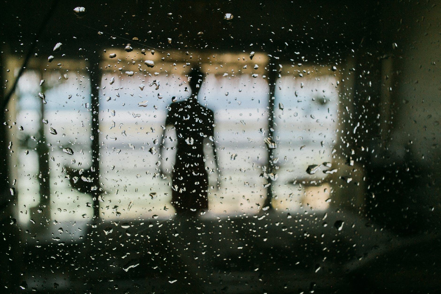 anonymous man behind window in raindrops