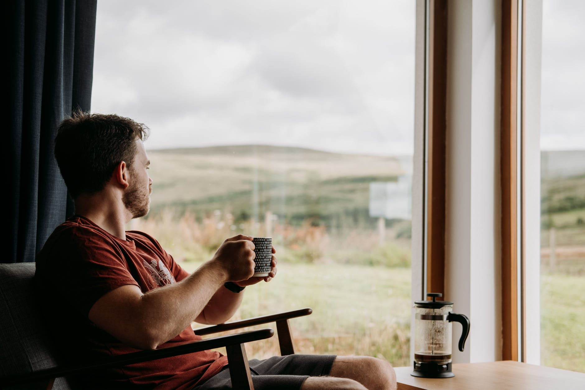 contemplative man with mug of coffee resting in armchair indoors