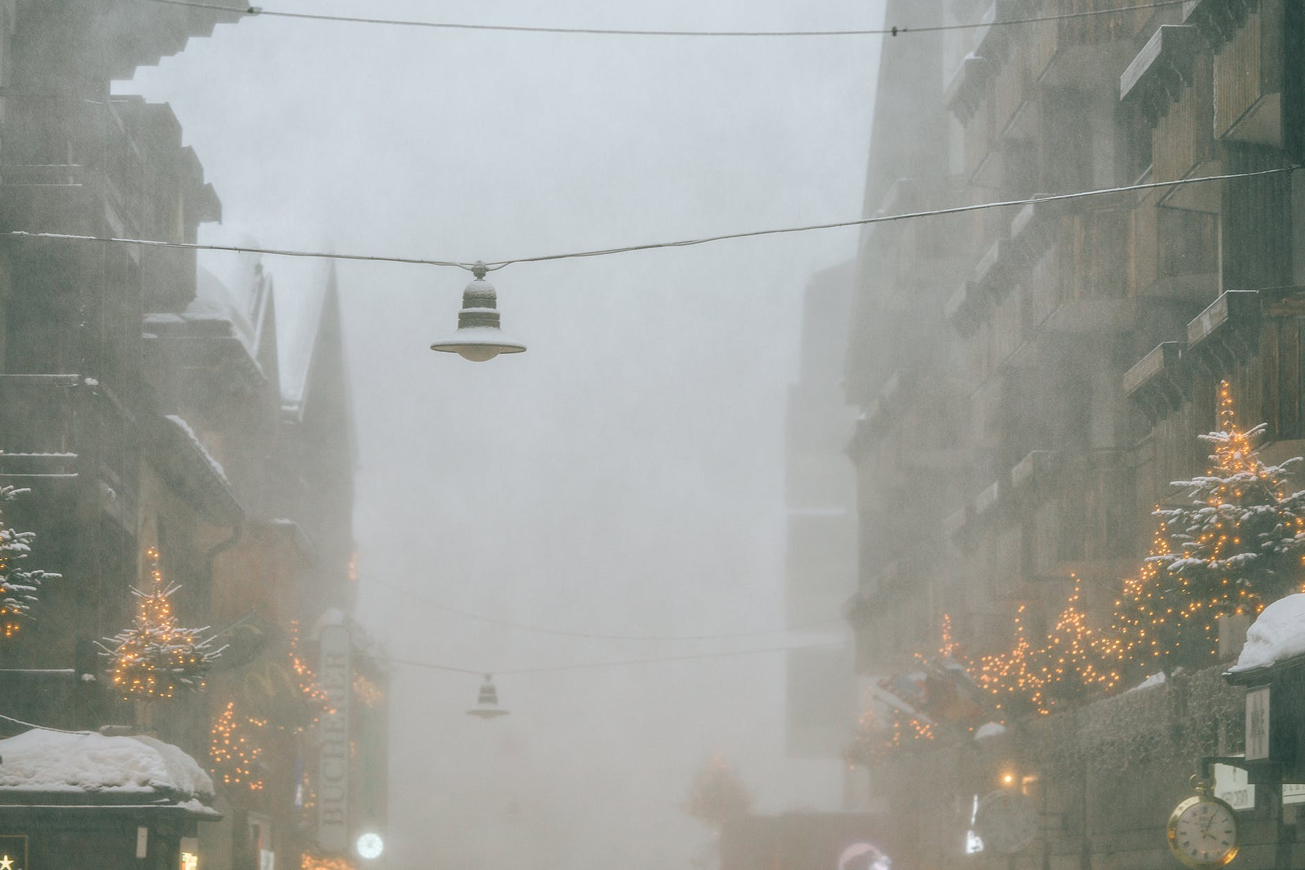 frozen city street with hanging streetlights on foggy winter day