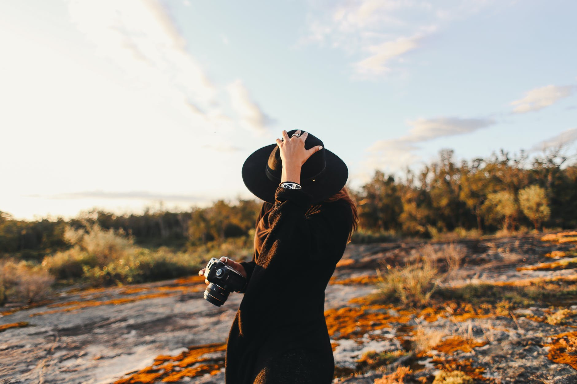 unrecognizable woman in hat and photo camera in nature
