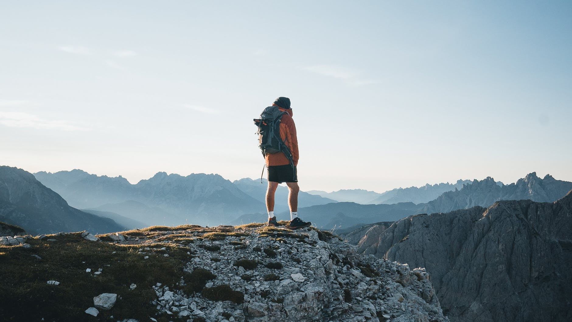 unrecognizable traveler standing on mountain top and admiring landscape