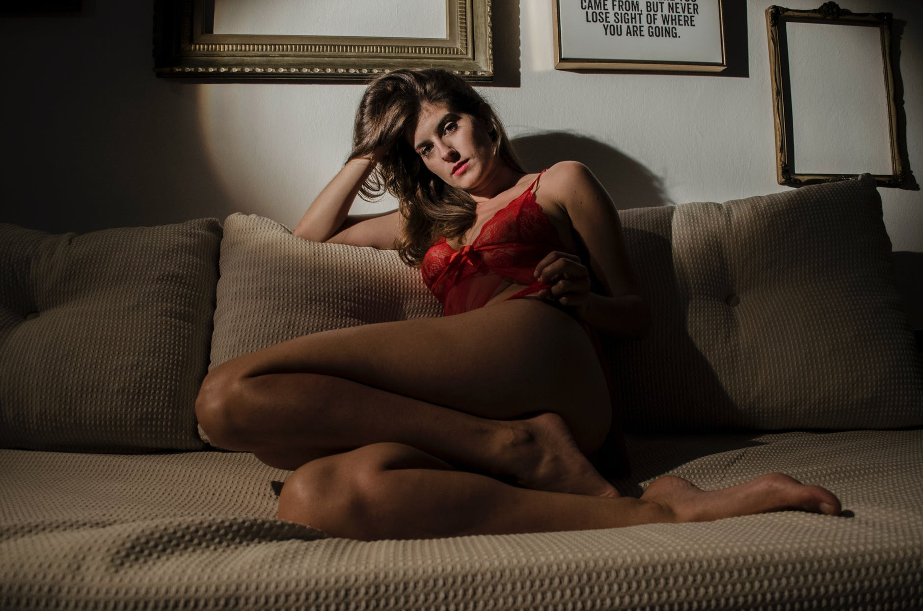 woman in red lingerie sitting on couch