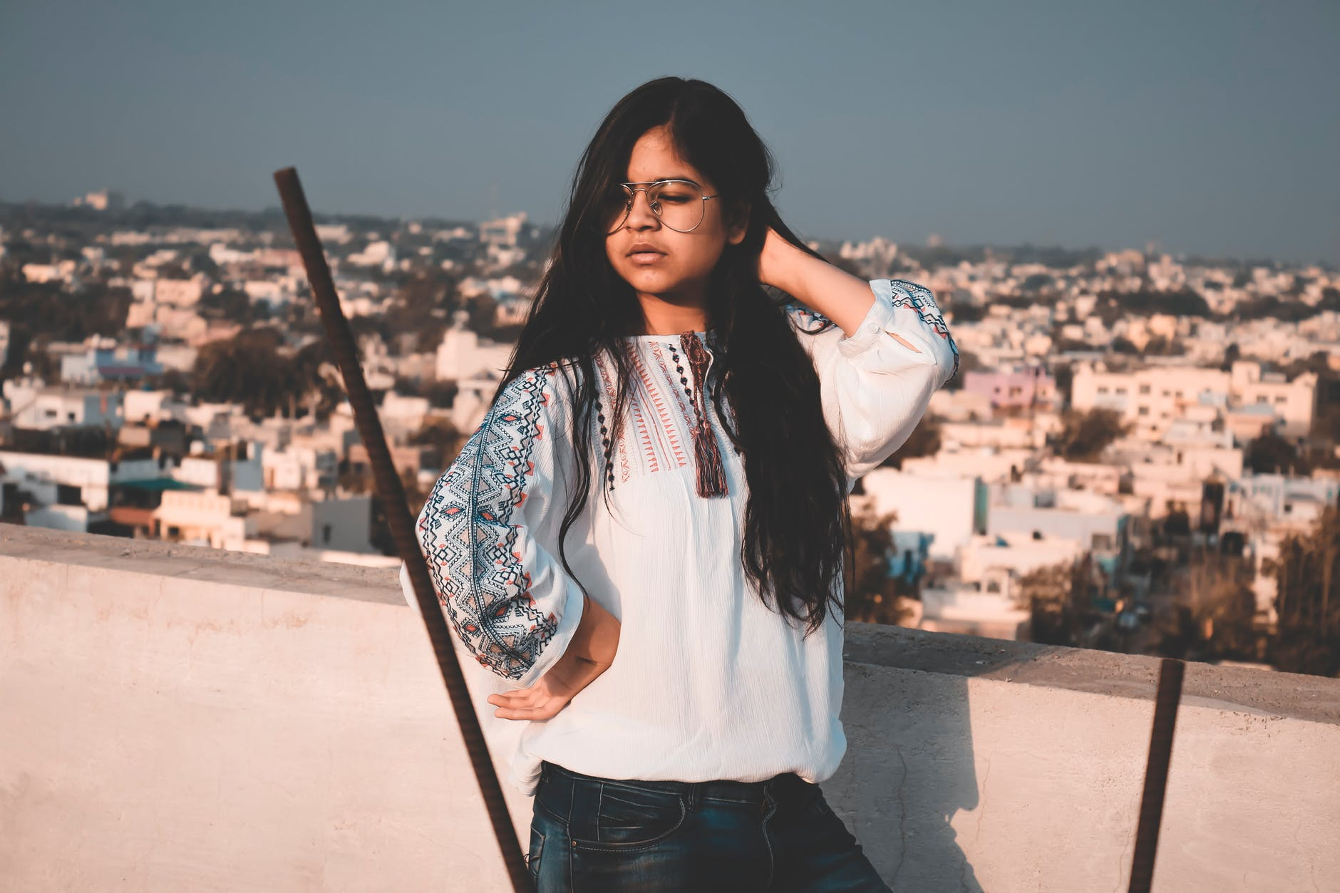 girl with long hair in white shirt standing on a balcony with view on city