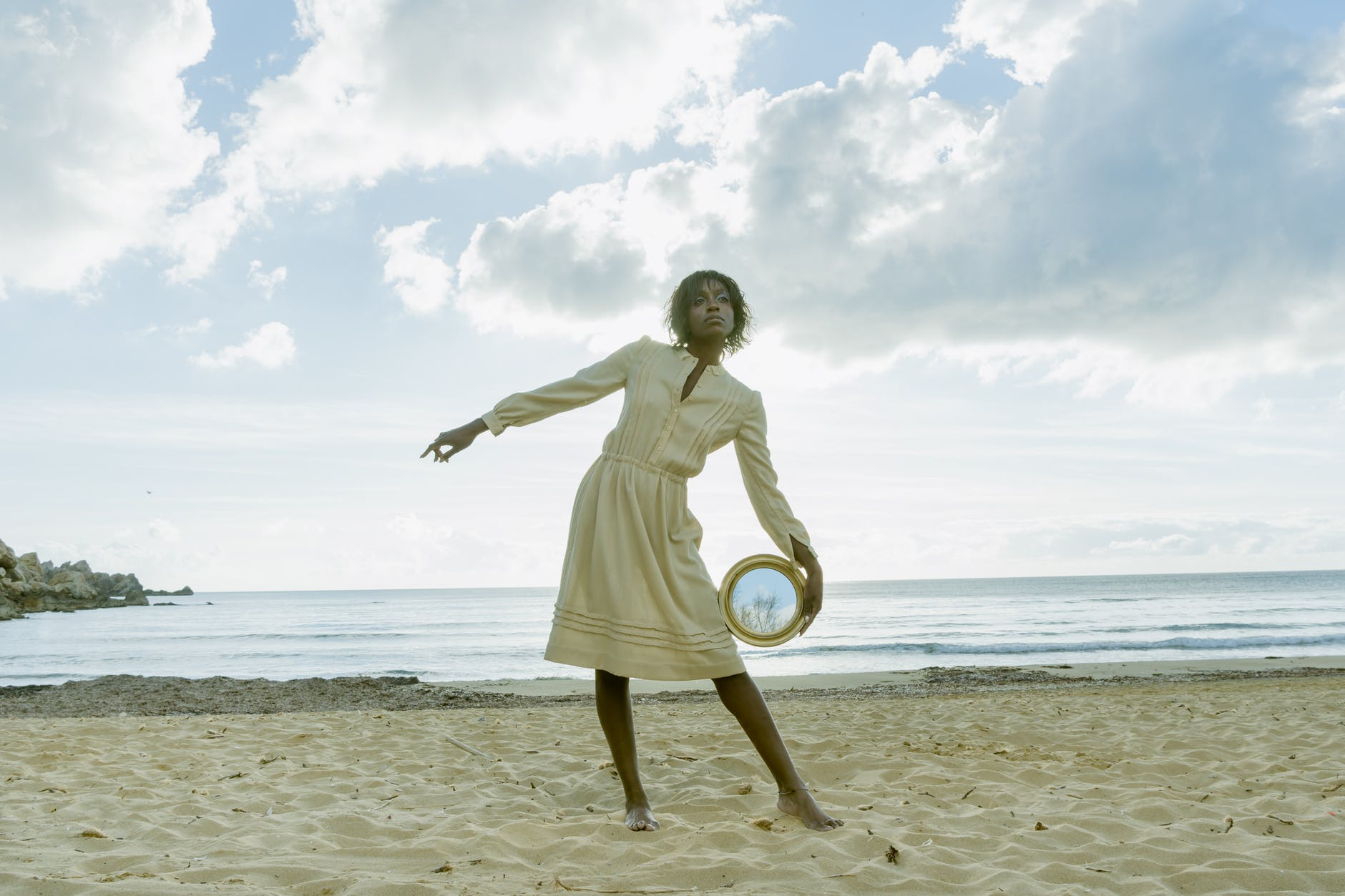 a woman posing in the beach holding a round mirror