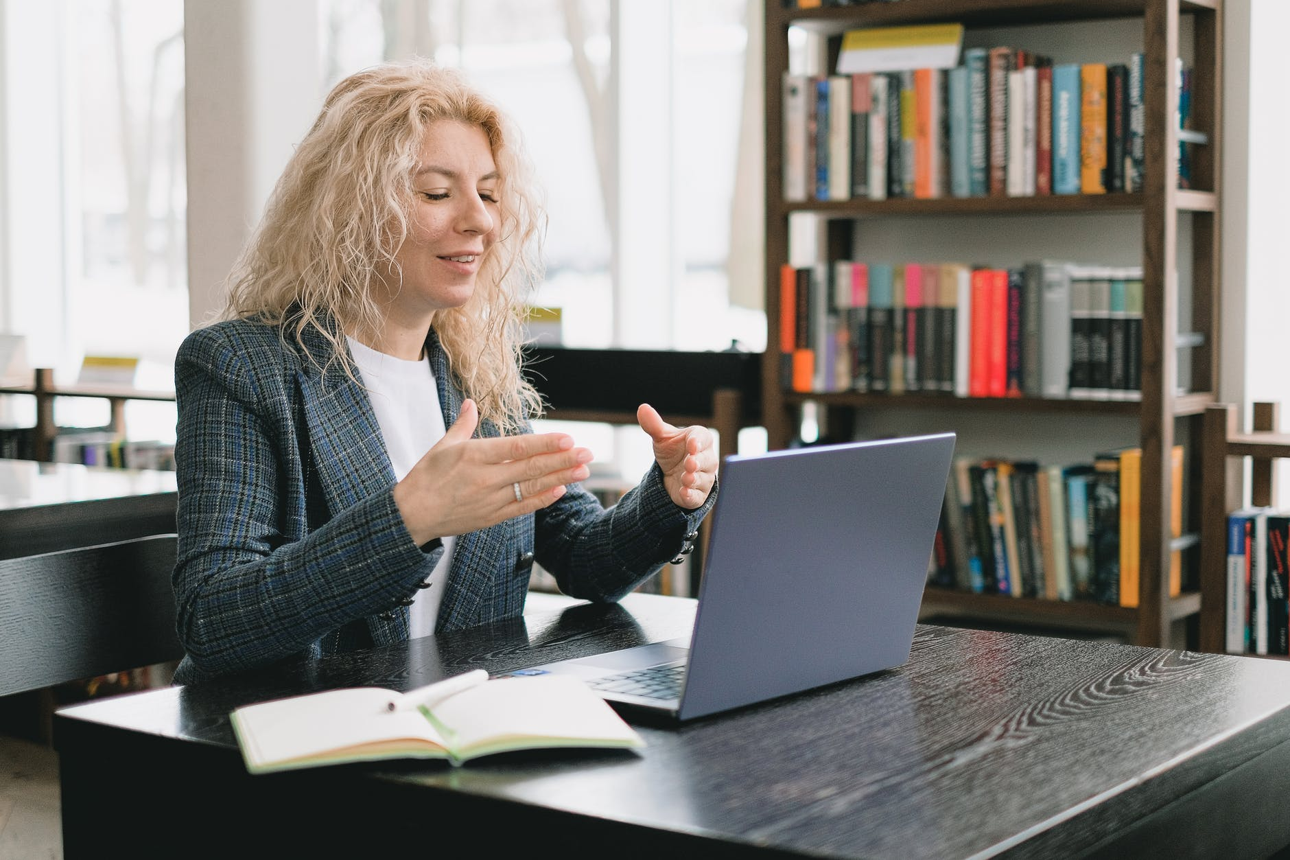 smiling woman having video chat via laptop in library