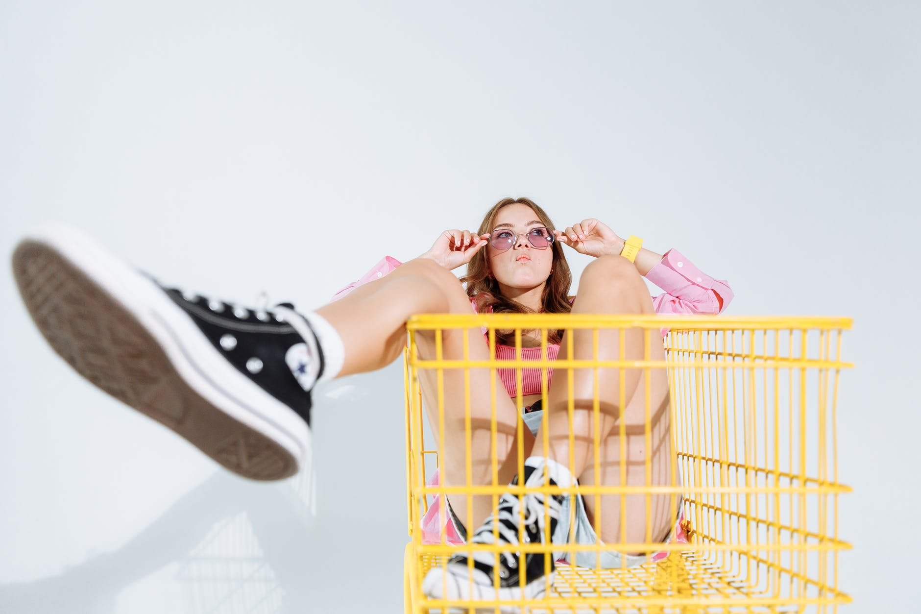 girl in black and white converse all star high top sneakers jumping on yellow shopping cart